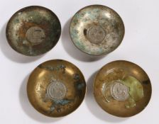 Set of four silver plated and brass Middle Eastern dishes, with coin inset bases and foliate