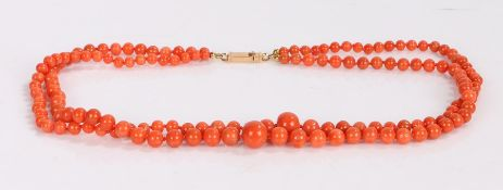 Coral necklace, the two stands of graduated coral beads with an 18 carat gold clasp, 47cm long