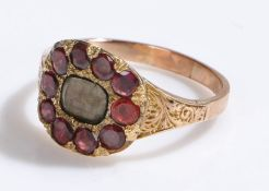 19th Century garnet set mourning ring, with a central glazed head with garnet surround, ring size O