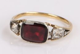 Garnet set ring, the rectangular garnet flanked by two paste stones, ring size J1/2