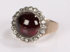 Garnet and diamond set ring, the cabochon cut garnet with a diamond set surround, ring size M