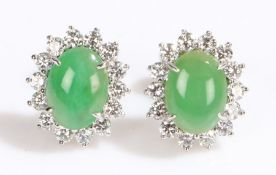 Pair of jade and diamond set earrings, the studs with a cabochon jade and diamond surround