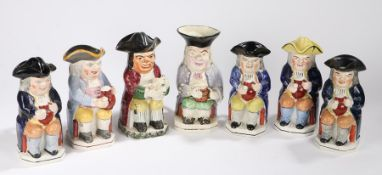 Collection of seven 19th Century Toby Jugs, all in a seated position holding jugs of beer, three
