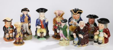 Collection of Staffordshire Toby Jugs, with seated examples in various colours, a standing Nelson