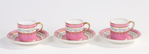 Three Victorian porcelain cup and saucers, decorated with bands of flowers with gilt borders on a
