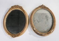 Two 19th Century oval framed mirrors, each housed within gilt frames and mounted with floral