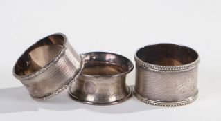 Three various silver serviette rings, various dates and makers, each with engine turned