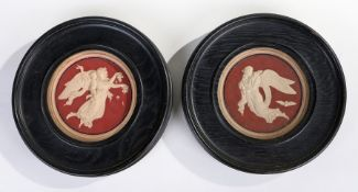 Pair of bisque porcelain wall plaques, the red grounds with raised depictions of cherubs and angels,