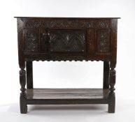 Mid 17th Century oak joined standing livery cupboard, the rectangular top above a lunette carved