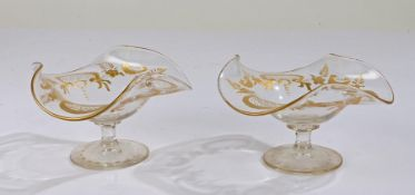 Pair of Victorian glass bon bon dishes, each with frilled rims and gilt floral decoration, raised on