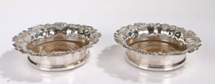 Pair of silver plate on copper bottle coasters, with pierced fruiting vine decoration and turned