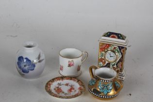 Three Royal Crown Derby miniature china items, in the form of a timepiece, mug and dish, together