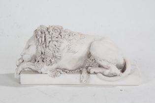 Lion ornament, in a white matt glaze, modelled lying down and raised on a rectangular base, 22cm