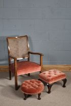 Cane backed arm chair upholstered in pink fabric together with two footstools upholstered in pink