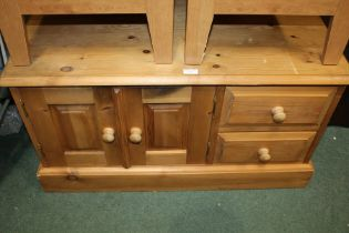 Pine low cupboard, the rectangular top abobe two drawers and two hinged doors, raised on a plinth