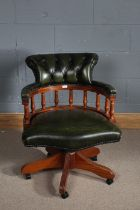 Contemporary green leather revolving desk chair, the button back above turned supports, raised on