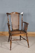 20th century beech elbow chair, having cane work back rest and seat, with spindle arm rests,