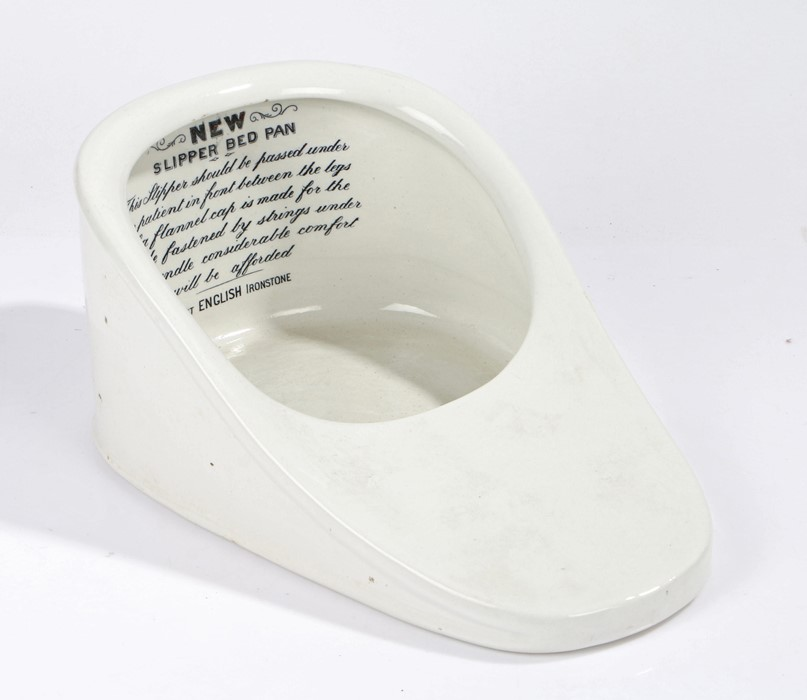 """English ironstone """"Slipper"""" bed pan, with instructions to the interior and a handle to the back"""