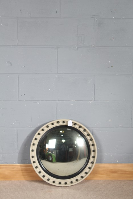 A painted convex mirror, the cream frame having black inner slip and ebonised ball decoration,