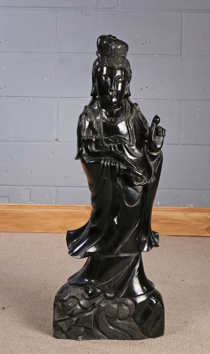 Substantial Chinese black hardstone figure, depicted holding a ruyi sceptre and a pearl, 94cm high