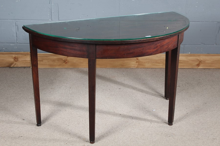 Edwardian mahogany demi lune table, with a glass top, raised on square tapering legs, 119cm wide