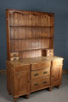 Early 20th Century pine dresser, the plate rack with three shelves and four drawers, the dresser