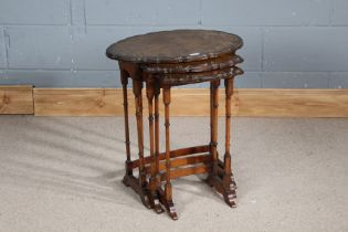 Nest of three 20th century walnut occasional tables, with piecrust tops and bamboo style legs,