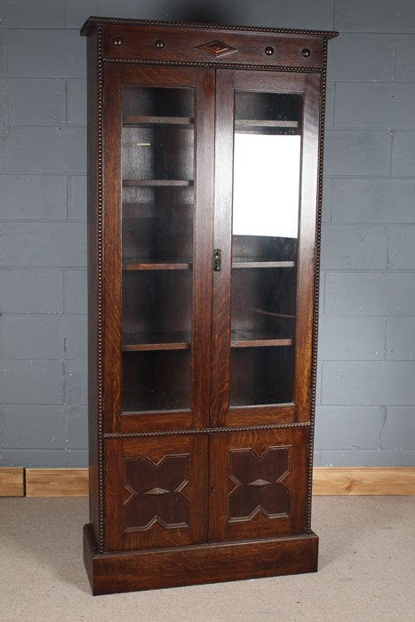 Early 20th century oak bookcase, having half roundels and geometric decoration above a pair of - Image 3 of 3