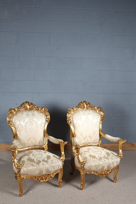 Pair of French style gilded armchairs, having carved pierced back with flowerheads, the open