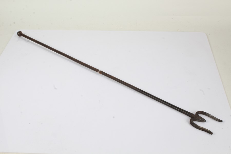 19th Century steel fire poker, of long proportions, with a knob finial, with a two prong end,