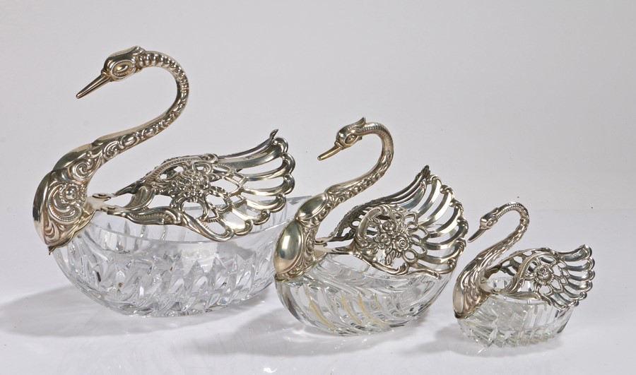 Graduated matched set of three silver mounted glass swans, the scroll and foliate bodies above