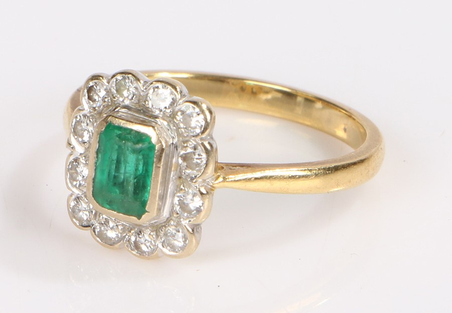 18 carat gold emerald and diamond set ring, the central emerald within the diamond set surround, 3.7
