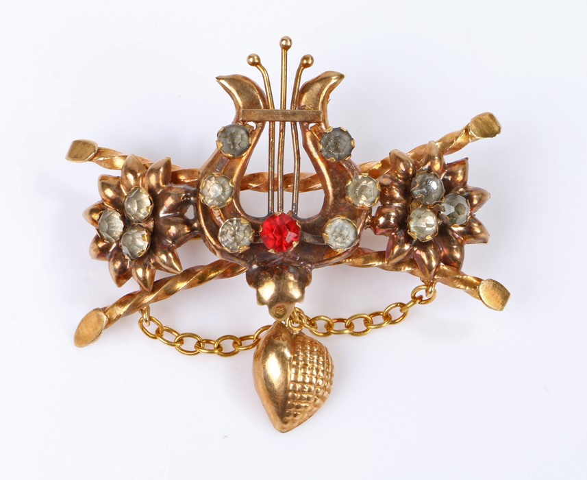 19th Century brooch, with a harp set with paste stone flanked by flower heads and twisted bars, 52mm