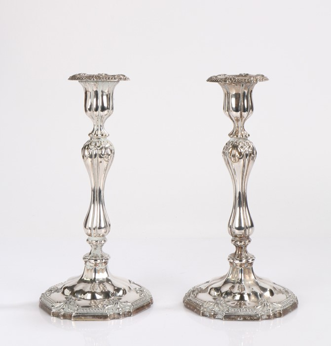 Pair of plated candlesticks, the hexagonal beaded and scroll decorated sconces above waisted