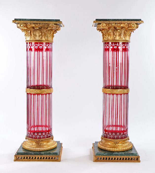 Pair of ruby and clear glass marble and gilt metal mounted columns, the green marble tops with