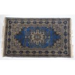 Machine made Persian design rug. The blue ground with foliate centre surrounded by a bird