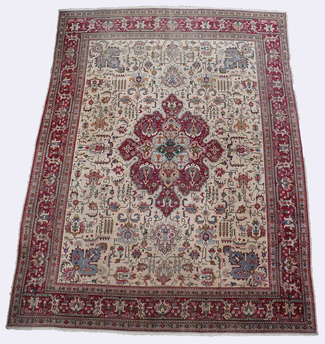 Tabriz carpet, the ivory ground centred by a rose red medallion within spandrels and all-over