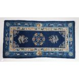 Semi antique Chinese rug, the blue ground with foliate decoration, 142cm x 76cm