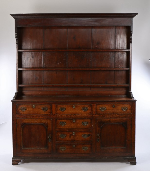18th Century oak dresser and rack, the concave cornice above three shelves and a rectangular top