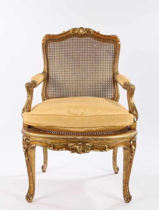 19th Century French giltwood fauteuil in Louis XV style, the foliate cresting above a cane back with