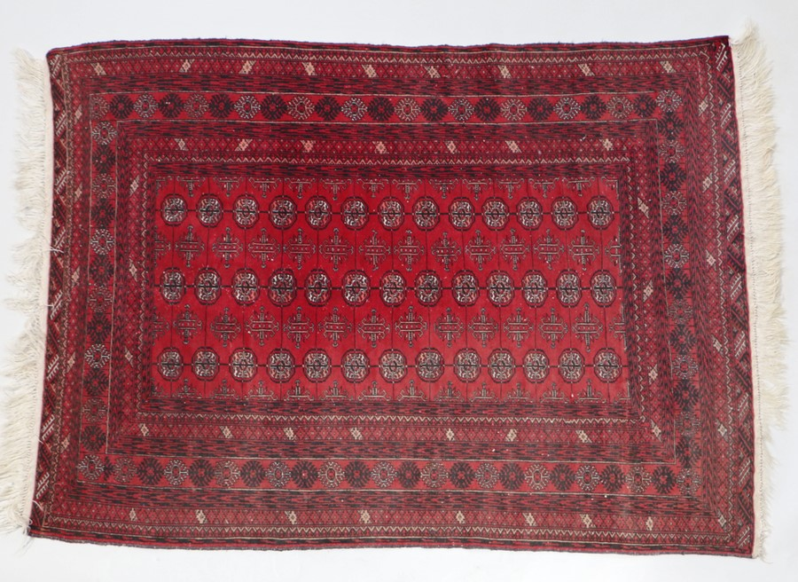 Modern red Afghan rug, the red ground with lozenge pattern centre, 168cm x 124cm