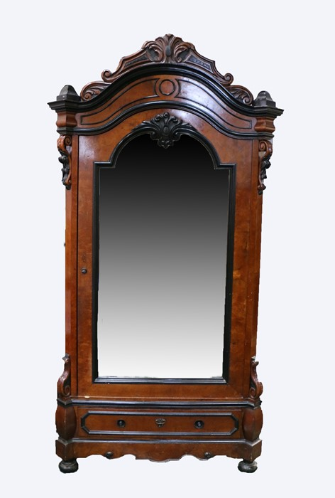 Late 19th Century armoire, the acanthus leaf pediment above large mirrored door with ebonised