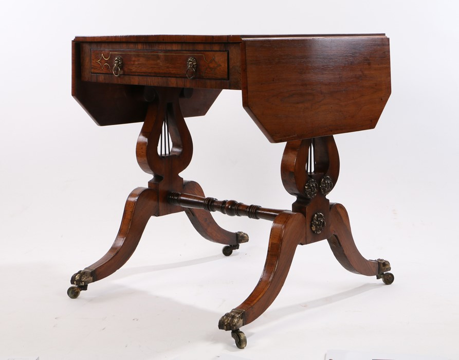 Small Regency rosewood and brass inlaid sofa table, the drop leaves with canted corners, with frieze