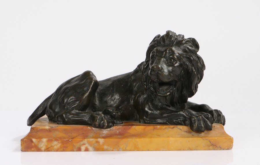 Victorian bronze of a reclining lion, raised upon a marble base, 21cm long, 10.5cm deep