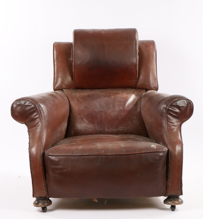 1920's leather deep armchair, with a large arched head rest and deep seat flanked by arms and raised