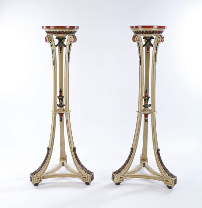 Pair of neoclassical style cream painted candlestands, with faux porphyry tops above leaf