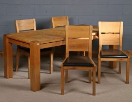 Light oak dining table, the rectangular top above four darker square legs, together with four