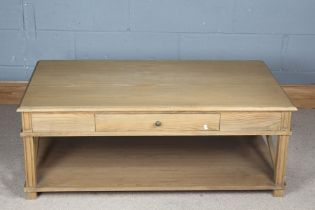 Light oak coffee table, the rectangular top above a frieze drawer, raised on square legs united by X