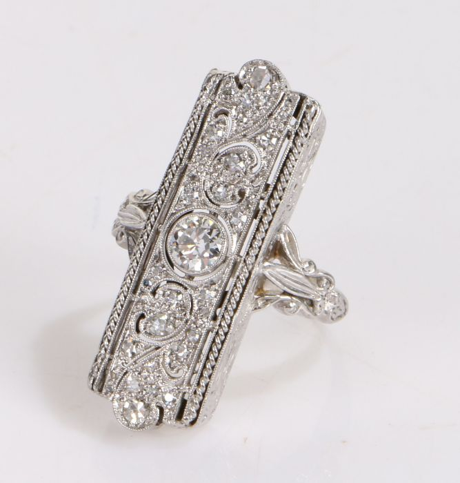 Diamond set ring, the rectangular set head with a round cut swag design, an estimated total