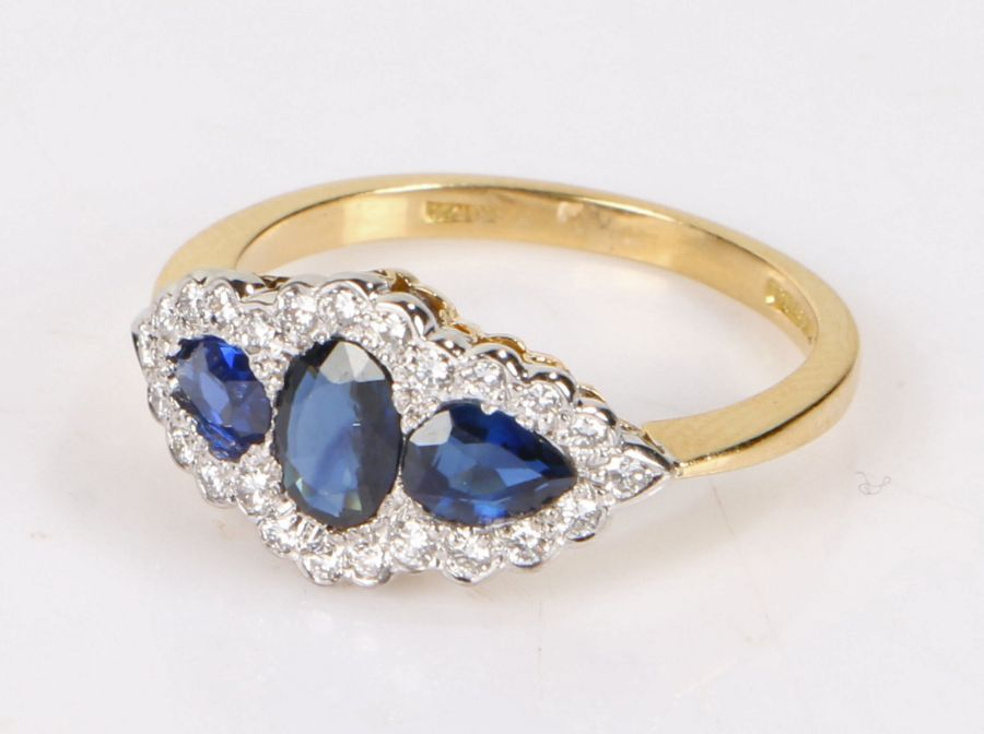 18 carat gold sapphire and diamond set ring, with three sapphires to the head at an estimated